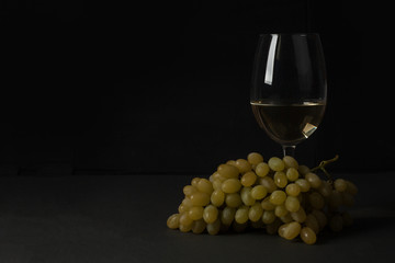 White wine in a glass with fall grapes, dark photo, dark background