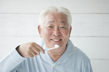 An elderly man is brushing his teeth