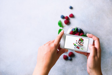 Girl is taking photos of breakfast, chia pudding with berries to mobile phone. Social media concept. Copy space, top view