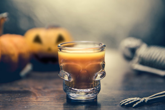Ideas for a children's and party of Halloween treats. Pumpkin orange cocktail in glasses, decorated with a pumpkin jack lantern, skelaton on a black wood table. Copy space