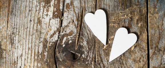 love concept on shabby chic wooden background. valentines day or wedding banner with tho hearts on old wood texture and copy space.