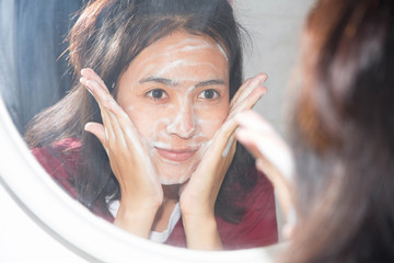 Young woman wash face with foam looking in mirror