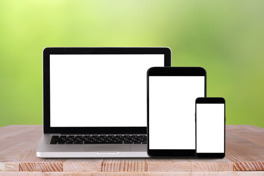Front view of the laptop, tablet pc, smartphone is on the work table with bokeh green background