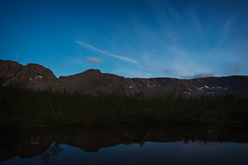 The sky with the stars at dawn, reflected in the water of a mountain lake.