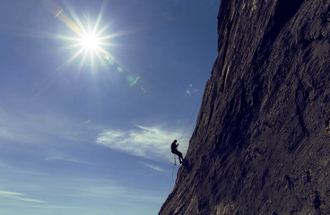 The climber makes a descent on a rope on the wall against the background of the sun.