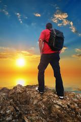 Man Tourist on the mountain edge and sunset sea sky