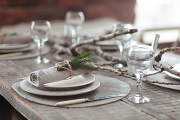 Rustic Christmas served wooden table with vintage silverware, candles and fir twigs. New Year Celebration, Christmas dinner served in loft interior