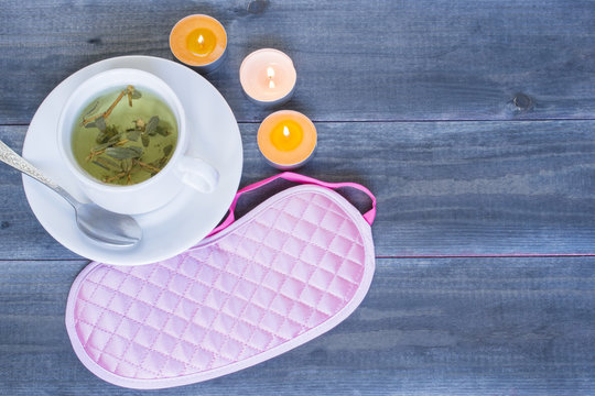 Good sleep concept, sleeping mask and a cup of herbal tea on the wooden table.