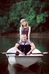 sweet girl staying near sitting guy on boat