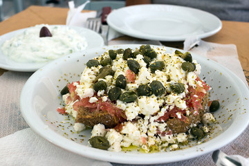 Dakos greek appetizer, dried bread, tomatoes, feta, or mizithra cheese, capers, oregano; Tzatziki in background. Taken in Naxos