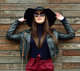 Beautiful brunette woman in sunglasses and in a hat  over wooden background. Street fashion. Outdoors.