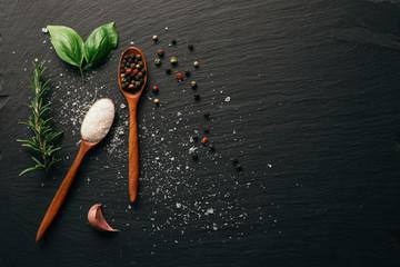 Sea salt and mixed peppercorn on dark black slate board. Top view. Copy space.
