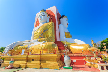 Illuminating Sunlight, Kyaik Pun Buddha the big Four Seated Buddha statues Shrine Sitting Back to Back of Four Directions on blue sky, Bago (Pegu), Myanmar.