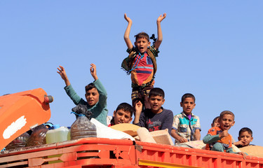 Displaced boys riding in a truck celebrate as they head back to their homes in Hawija, on the outskirts of Kirkuk
