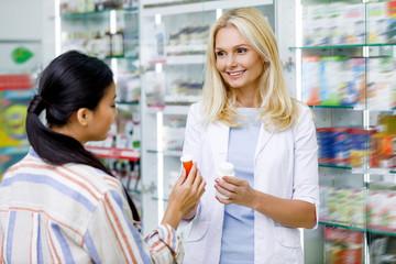 pharmacist consulting customer in drugstore