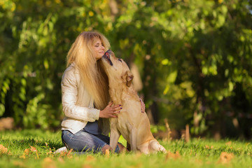 Lovely scene of beautiful long haired blond girl hugging with her favorite dog in the park