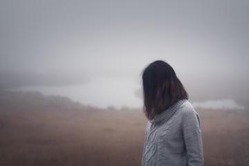 Depressive Frau steht am Wasser im Nebel