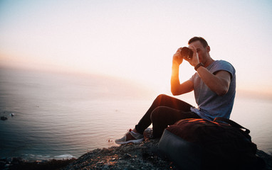 Young male Adult taking photos with camera while sitting on edge of mountain