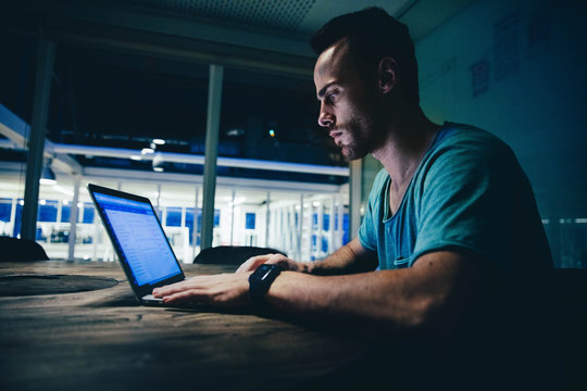 Young Businessman working late on his laptop in modern office