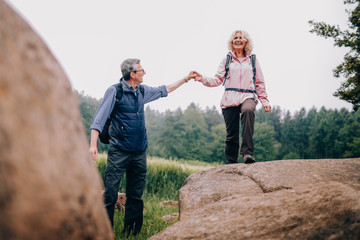 Senior Man helping his wife climbing up a rock on hike