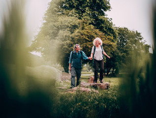 Mature Couple hiking trough beautiful green fields