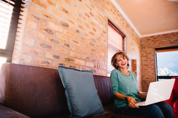 Woman having fun laughing with her laptop on couch at home
