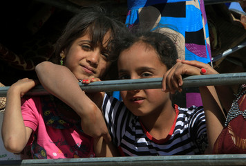 Displaced children ride in a truck with their families as they head back to their homes in Hawija