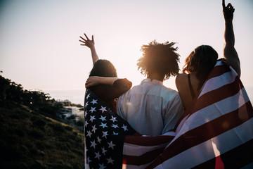 Group of millennial friends holding USA flag