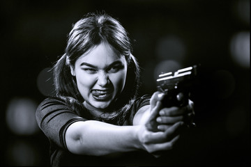 fun girl with gun on blurred background aiming at camera, show tongue, monochrome