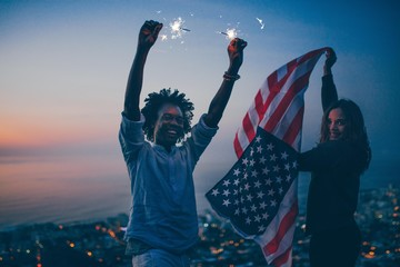 Couple celebrating with sparkler and USA flag at night