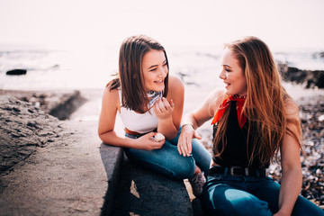 Teenager girls having fun chatting on the beach