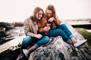 Happy Young teenager girls looking at smart phone and laugh