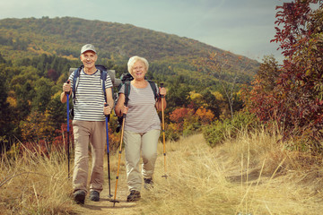 Two elderly hikers walking towards the camera outdoors
