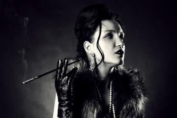 beautiful female retro style portrait with cigarette on dark background, monochrome