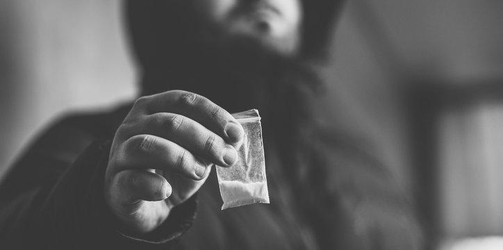 Drug dealer selling drugs junkie. Drug abuse concept and overdose concept. Mans hand holds plastic packet with cocaine powder