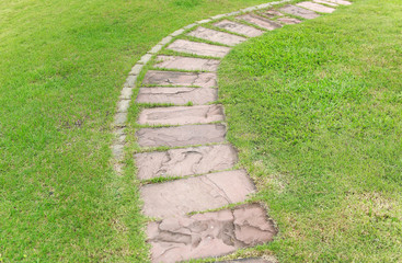 Stone walkway in the park with green grass background.