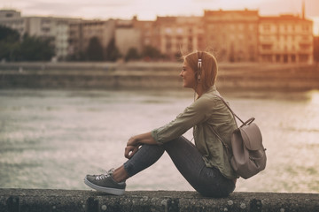 Young woman enjoys listening music while sitting at the riverbank.