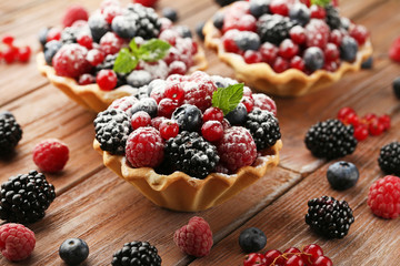 Tasty tartlet with berries and powdered sugar on brown wooden table