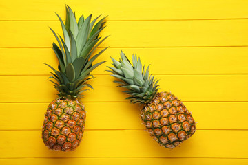 Ripe pineapples on yellow wooden table
