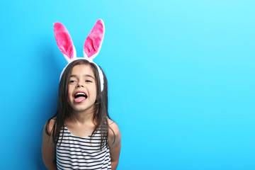 Beautiful little girl with rabbit ears on blue background