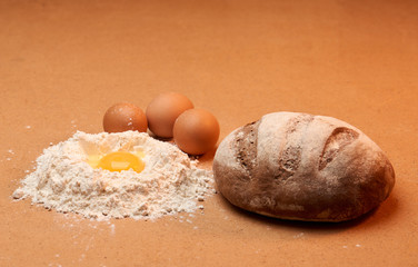 The bread, three eggs and an egg yolk surrounded by flour