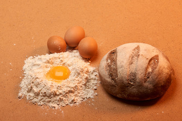 The round bread, three eggs and an egg yolk surrounded by flour