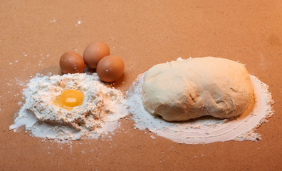 The dough, three eggs, and egg yolk, surrounded by flour