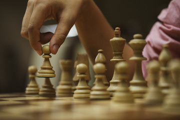 on a chess game, a chess player makes a move with a pawn