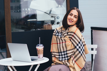Portrait of a young woman holding her laptop computer while sitting on a chair