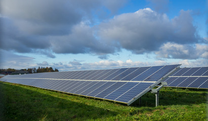 Solar panel or photovoltaic farm on green field with dramatic cloudy sky in North Germany
