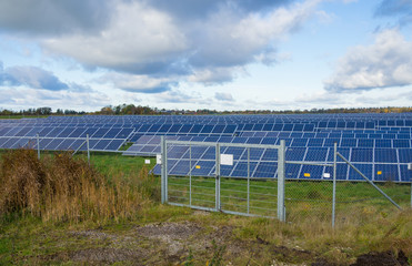 Solar panel or photovoltaic farm behind metal chainlink fence on green field with dramatic cloudy sky in North Germany