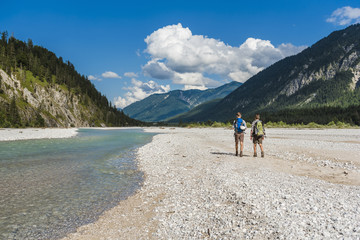 Germany, Bavaria, back view of two hikers with backpacks walking in dry creek bed