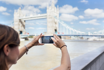 UK, London, woman taking a picture of the Tower Bridge