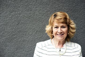 Portrait of smiling senior businesswoman against grey wall